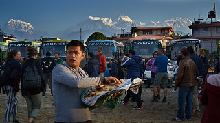 Nepali seller at tourist bus stop in front of Annapurna massif, Pokhara, Nepal