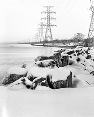 Rocky shores and power lines (Brian Copeland Photography) Tags: ilforddeltaprofessional100 selfdeveloped winter burlingtonskyway powerlines stillcamera omega45d rodenstocksironarcopal1210mmf56 outdoor blackandwhitefilm weather lakeontario snow viewcamera seasons photogear orangefilter filter outside burlington northamerica dilutionb largeformat ontario canada kodakhc110 ilford film ice 4x5 copal1 copalno1 ilfordfilm omega rodenstock sironar toyo blackandwhite exterior lensfilter monochrome season wintertide wintertime hamilton ca