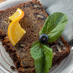 Close-up of a slice of banana bread, garnished with mint leaves and an orange slice thumbnail