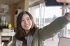 Young woman taking selfie picture in cafe (Apricot Cafe) Tags: img72857 asia asianandindianethnicities healthylifestyle japan japaneseethnicity tamronsp35mmf18divcusdmodelf012 autumn autumnleafcolor candid carefree casualclothing charming cheerful chibaprefecture colorimage enjoyment forest handraising happiness indoors leisureactivity lifestyles lookingup mountain oneperson onlyjapanese outdoors people photograhing photography realpeople relaxation restaurant selfie smartphone smiling sunlight sustainablelifestyle toothysmile tourism tourist traveldestinations waistup weekendactivities women youngadult kimitsushi chibaken jp