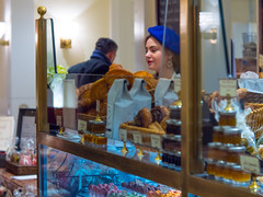 The Discreet Charm of the Patisserie (Mildred Alpern) Tags: woman employee patisserie cakes cookies counter indoor food glass muffins jams confection