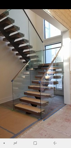 Ultra modern freestanding staircase, with open risers, glass railing and metal handrail by #andronxStairs in Charlotte NC.
