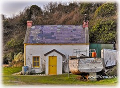 Old fishermans cottage, Inch Island, Co. Donegal. (willieguildea) Tags: cottage house building inchisland donegal ireland eire ulster scenic landscape nikon boat fishingboat grass garden
