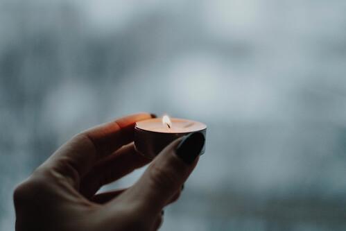 Girl's hand holding burning candle. Winter background.