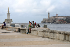 On the Waterfront (Poocher7) Tags: people portrait camera tourist fishermen waterfront bayofhavana ocean fence poseiden statue wall water gulfofmexico lighthouse fortress cannons castillodelostresreyesdelmorro castle cloudy sundaylights hff ironfence