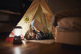 Young Boy Reading Inside Tent Set Up Indoors