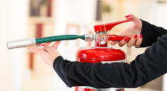 Closeup woman hands with red nailpolish showing how to operate fire extinguisher (longislandfireprotection) Tags: