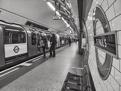 Impatience (Douguerreotype) Tags: train monochrome underground city bw station uk sign metro british england mono blackandwhite tunnel britain urban subway london gb people tube