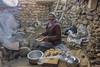 Baking thagi kambir (tmeallen) Tags: thagikambir puffedbread dungfire woman smiling bakingbread outdoorkitchen stonewall smoke traditionalattire traditionalbread ladakh lammuandkashmir himalayas india