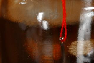 Ein roter Faden im Nadelöhr in einem Fläschchen