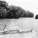 Oskar Speck standing in river beside his kayak SUNSCHIEN