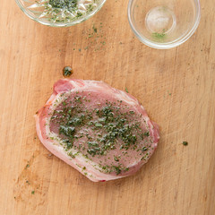 Marinating pork fillet. (annick vanderschelden) Tags: oil cookingoil herbs ingredients herbesdeprovence parsley thyme chives marjoram rosemary marinade board wood bowl glass decorative red food culinary whitepepper pepper brush