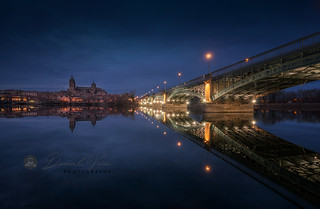 Night view of the Cathedral of Salamanca with Enrique Esteban bridge lit foreground and reflections in the Tormes river, Salamanca, Spain