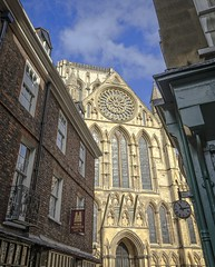 Yor Minster between two buildings. (jack cousin) Tags: yorkuk yorkshire yorkminster minster famous church exterior worship medieval christianity christian history historic stone old masonry stonework building landmark heritage city ancient localicon sky bluesky cloud clock balcony