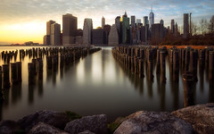 The way to NY (Gary Walters (offline for a bit)) Tags: brooklyn longexposure nyc sunset manhattan financialdistrict newyorkskyline sonya7r city cityscape pilings piers sel1635z light water rock river sky clouds iconic landscape