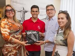 André recebe o kit do Sesc da presidente do Sindivarejo Caicó e do presidente da Fecomércio RN, acompanhado pela mãe