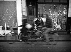 Phi (Wormsmeat) Tags: amsterdam street bikes bicycles phi greek alphabet shopping blur hat scarf road window shop mobile phone olympus penf 12100mzuikopro streetphotography netherlands holland riders commuters