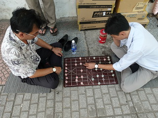 Men playing Chinese Chess on the sidewalk