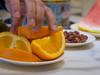 Reaching (Mildred Alpern) Tags: orange slices hand fingers watermelon peanuts table plates indoors fingernails