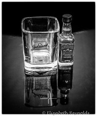 Day 39. (lizzieisdizzy) Tags: blackandwhite blackwhite black whiteandblack white whiteblack reflections reflection reflective red glass bottle whiskey jackdaniels table tabletop mirrormirrorreflection signature trademark miniature label labelled screwlid squareglass tumbler shoglass