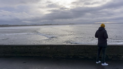 Guy looking at the ocean on a rainy day (gute_laune) Tags: horizon sunny natural ireland nature young tourist background jacket sea looking male beach ocean outside sky europe presentation view authentic guy landscape sunset back person couldy light countryside man beanie traveler travel dark freedom sun rainy summer behind sunrise happy westcoast