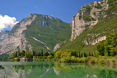 At the Lago di Toblino in midsummer (echumachenco) Tags: lagoditoblino lake water reflection trentino italy italia italien green sky blue cloud outdoor landscape serene summer july cypress mountain mountainside cliff wall face forest wood vegetation plant nikond3100 grass