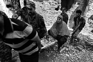 In the ruins old city of Mosul, members of the Federal Police carry an old woman unable to escape the fights.