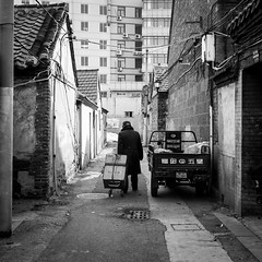 Heavy road (Go-tea 郭天) Tags: yantaishi shandongsheng chine cn yantai alley narrow hutong old ancient traditional tradition history historical historic man candid alone lonely boxes carry carrying trolley dirty dirt motorbike motorcycle electric electricity cables lines back backside cap cold winter day sun sunny shadow walk walking street urban city outside outdoor people bw bnw black white blackwhite blackandwhite monochrome naturallight natural light asia asian china chinese shandong canon eos 100d 24mm prime