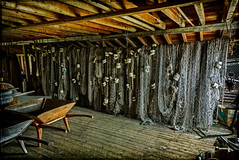 Fishing nets for the cod trap hanging in the store (fisherman's waterfront building for processing fish and storing gear) (Brett of Binnshire) Tags: historicbuilding industry broompoint historicalsite lightroomhdr lrhdr manipulations highdynamicrange locationrecorded shed grosmornenationalpark architecture canada hdr newfoundland commercialfishing equipment net wheelbarrow
