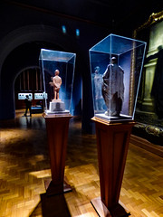 Tapered (Steve Taylor (Photography)) Tags: cabinet display art sculpture statue museum painting mauve purple brown green violet glass men man uk gb england greatbritain unitedkingdom london perspective reflection nationalportraitgallery terracottastatuette1873 exlucelucellum robertlowe caricaturistcarlopellegrini clay