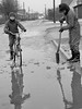 Helping the town after the flood (theirhistory) Tags: boy road street pavement ice water drain blocked spade bikr bicycle hat jacket wellies balaclava boots child kid