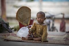 A fresh breeze by a child in Mandalay, Myanmar (Tim van Woensel) Tags: mandalay child burma myanmar street hand fan rug eyes asia travel bicycle sandal mahamuni buddha temple