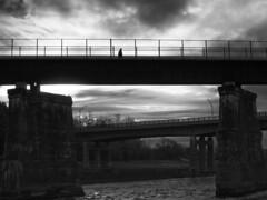 Solitary Walk (delmarvajim) Tags: bw blackandwhite moody bridge walker river clouds dark fineart