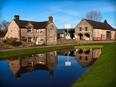 reflections of Hartington (jeff.dugmore) Tags: england uk britain derbyshire peakdistrict whitepeak nationalpark europe peaknationalpark hartington village water grass pond pool reflection duckpond green buildings sign architecture limestone blue sky outside outdoors walking hiking drystonewall tree spring march vignetting olympus stone