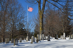 Pittsford Cemetery in the Snow (dr_marvel) Tags: ny pittsford rochester newyork snow pole flag usflag graves stones tombstones white blue flagpole