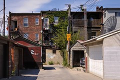 Back alley vista, Little Italy, Toronto. (edk7) Tags: nikond50 edk7 2007 canada ontario toronto littleitaly behindcollegestreet architecture building oldstructure residential commercial backalley lane laneway city cityscape urban brick wall graffiti rusty electricitywire hydrowire communicationcable duct stair fence vinylsiding concreteblock tree balcony satellitedish trash rust truck vehicle automobile auto weatheredwood garage door insulbrick