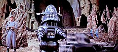 """Debut of Robby the Robot in """"Forbidden Planet"""" (1956) (lhboudreau) Tags: movie film motionpicture hollywoodmovie sciencefiction forbiddenplanet mgm metrogoldwynmayer 1956 classicmovie vintagescifi vintage classic scifi 1950s story nicholasnayfack fredmwilcox fredwilcox irvingblock allenadler altair altairiv planet remoteplanet alienlandscape rock rocks outerspace thetempest krell featurefilm robot robbytherobot robby gun guard landtransport transport debut firstappearance screenshot"""
