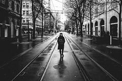 angus young (matthias hämmerly) Tags: switzerland candid street streetphotography shadow contrast grain ricoh gr black white bw monochrom monochrome city town urban blackandwhite strasse people monochromphotography dark zürich zuerich rain lonely cold winter swiss einfarbig linien gebäude bahnhofstrasse woman bag walk alone rails tram
