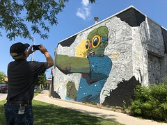 Elbows out (KevinIrvineChi) Tags: hebru brantley mural west loop iphone outdoors restaurant flybou flyboy chicago illinois man photographer photo photographing hat ball arms up elbows out green goggles black white blue public art publicart trees grass bushes bush sidewalk pavement street sunny sky fist mouth open artist boingboing 1400 w randolph ogden ave avenue