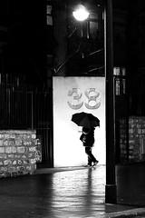 Under the lit lamppost (pascalcolin1) Tags: paris13 femme woman nuit night pluie rain neige snow lampadaire lamppost reflets reflection porte door photoderue streetview urbanarte noiretblanc blackandwithe photopascalcolin 5omm canon50mm 50mm parapluie umbrella