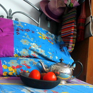 tea and tomatoes on unmade bed