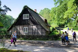 DSC_9862 Reetdachhaus, Fachwerkgebäude im Dorf von Wilsede / Lüneburger Heide - Straße mit Kopfsteinpflaster, Wegweiser für die unterschiedlichen Wanderwege.