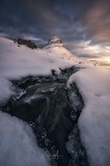 Rushing Water under the Mountain Peak (Manuel.Martin_72) Tags: iceland darkmood drama enchanting lightdrama magic ice mountainpeaks mountainslope mountains riverbed rocks stones cascade frozen reflections river snow water waterfall clouds cloudy glow morning sunrise wbpa kirkjufell