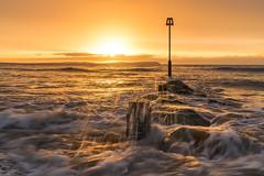 sunrise and waves (Anthony White) Tags: christchurch england unitedkingdom gb 7rm2 sunrise orangesunrise crashingwaves litwaves nopeople seascape natur nature naturaleza rocks ocean