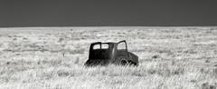 Half Shell on the Plains (unknown quantity) Tags: monochrome bleak horizon abandonedvehicle shadows rust blackandwhite weathered grass oxidation hss