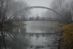 Foggy mornings (The Frustrated Photog (Anthony) ADPphotography) Tags: category citiestowns eskisehir kanlikavakpark places travel turkey citypark park river watercourse water reflections reflection bridge metal pattern shape people cycle cycling walking riverbank fog foggy grass sky trees outdoor landscapephotography travelphotography canon1585mm canon70d canon mist tree landscape