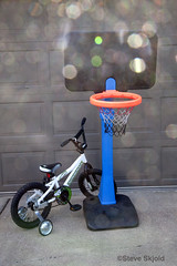 Spotted hoop and bicycle. (Spike's Shoes) Tags: small basketball hoop bicycle training wheels childs kids vertical outdoors outside daytime daylight mahtomedi minnesota usa c5530143 sunspots abstract