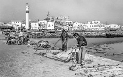 Sicilian Fishermen tending their nets (1982) (FotoGrazio) Tags: 1982 documentaryphotography europe fishermen italy mediterranean sicilians sicily streetphotography waynegrazio waynesgrazio worldphotographer classicblackandwhite composition filmphotogrpahy fotograzio internationalphotographers men nets people photojournalism pier retro socialdocumentary street streetscene travel travelphotography vintage