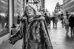 The Shopping Trip (Leanne Boulton) Tags: portrait people urban street candid portraiture streetphotography candidstreetphotography candidportrait streetportrait eyecontact candideyecontact streetlife woman female face expression eyes look emotion feeling mood atmosphere fur furry coat fashion glasses tone texture detail depthoffield bokeh naturallight outdoor light shade shadow city scene human life living humanity society culture canon canon5d 5dmkiii 70mm ef2470mmf28liiusm black white blackwhite bw mono blackandwhite monochrome glasgow scotland uk