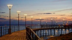 Sunset by the Pier - Limassol, Cyprus (Andreas Komodromos) Tags: cyprus limassol mediterrenean pier sea streetlight sunset travel water winter sky clouds europe walkway shadows light sunlight lamp reflections vacation flickrtravelaward waterfront streetlights shadow reflection sony6000 noflash exposure city boardwalk allfreepicturesmarch2018challenge landscape seascape